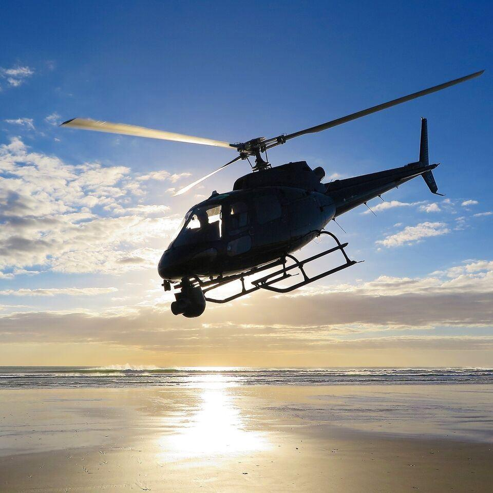 helicopter with mounted camera flying over ocean