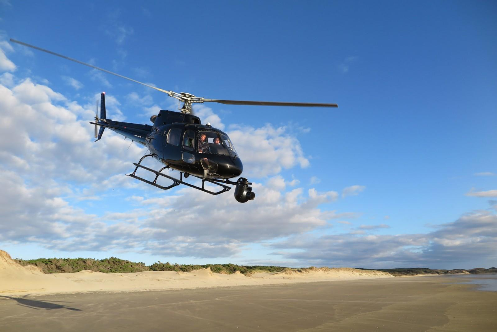 helicopter flying over sand dunes with gyroscopic camera mounted on nose